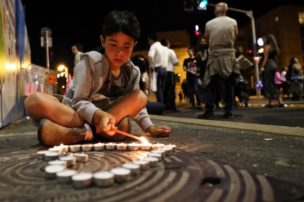 A boy lights candles in a heart shape during a vigil for the people killed and injured in the stampede