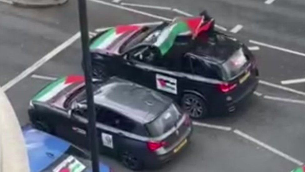 A grab from the video filmed and shared on social media, it shows two cars parked at traffic lights with Palestinian flags