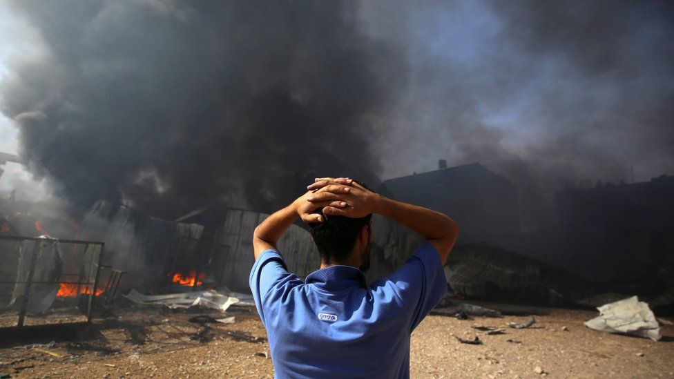 A man stands near a burning sponge factory after it was hit by Israeli artillery shells in Gaza