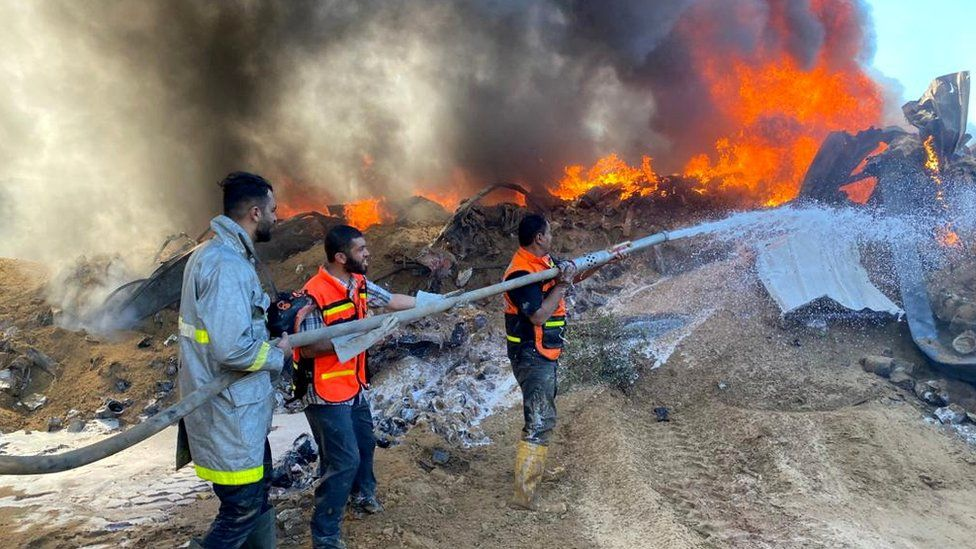 Firefighters hose a blaze at a warehouse in Rafah, Gaza (18 May)