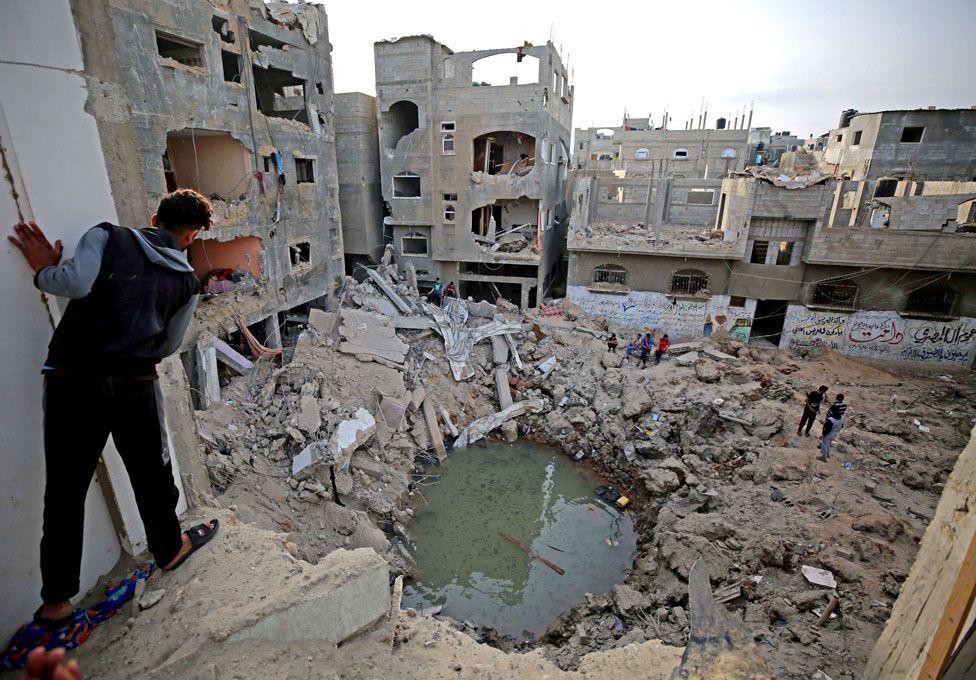 People stand around and look at their bomb-damaged homes in Gaza following a ceasefire with Israel