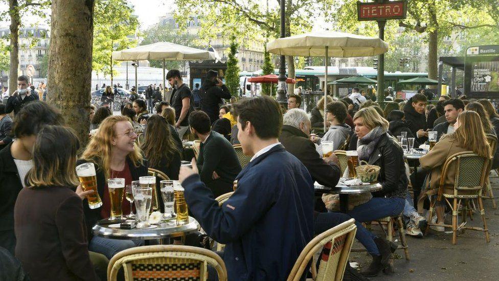 Customers drink beers at outdoor terraces in Paris