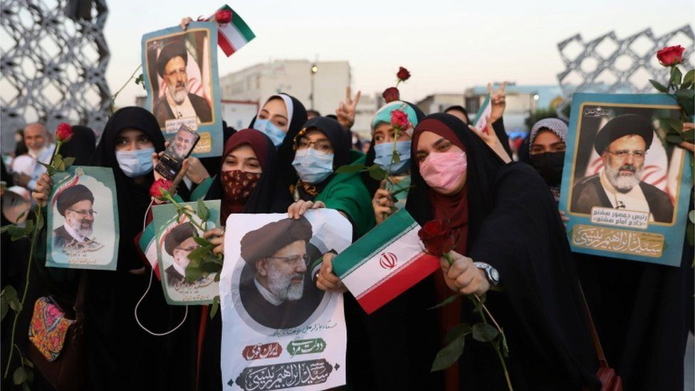 Supporters of Ebrahim Raisi hold up his portrait and roses
