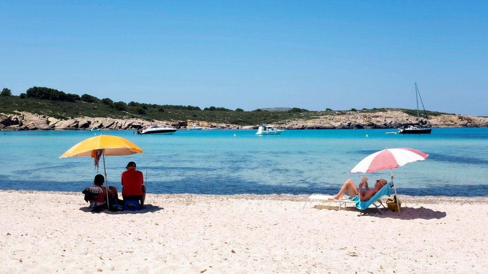 People enjoy warm weather at a beach in Menorca
