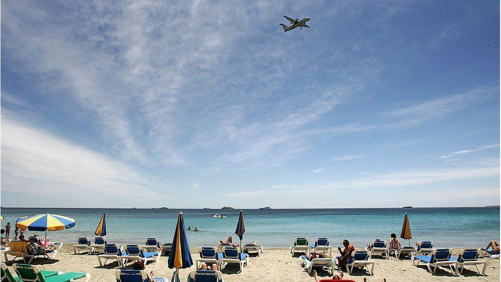 Plane flies over a beach in Ibiza