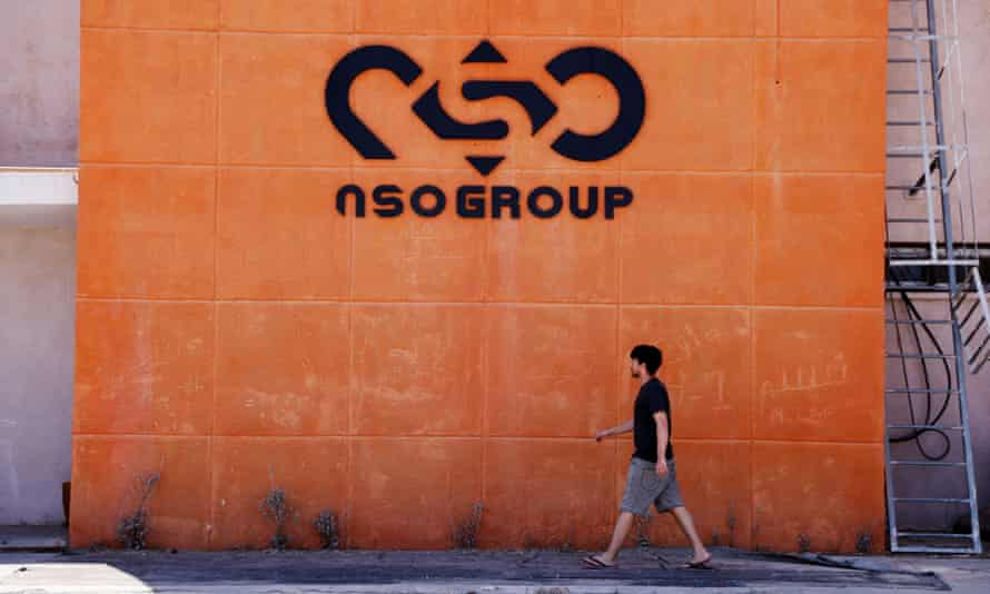 A man walks past the logo of NSO Group at one of its locations in southern Israel
