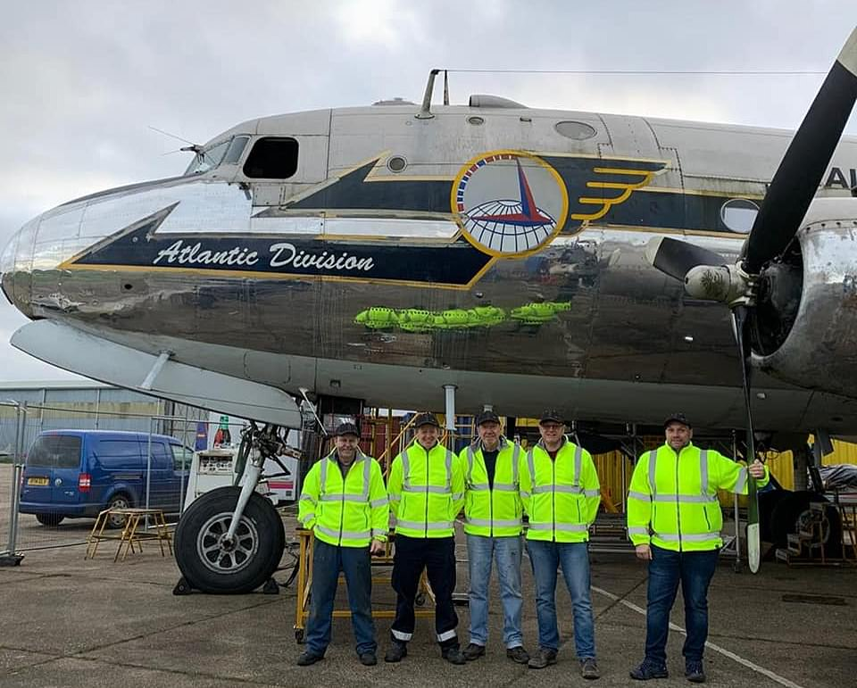 She will fly again: The 1945 Douglas C-54 Skymaster that was saved from a scrapyard is undergoing a £1 million refurbishment by veterans and volunteers to return it to its former glory. Pictured: Volunteers with the plane atNorth Weald Airfield in Essex