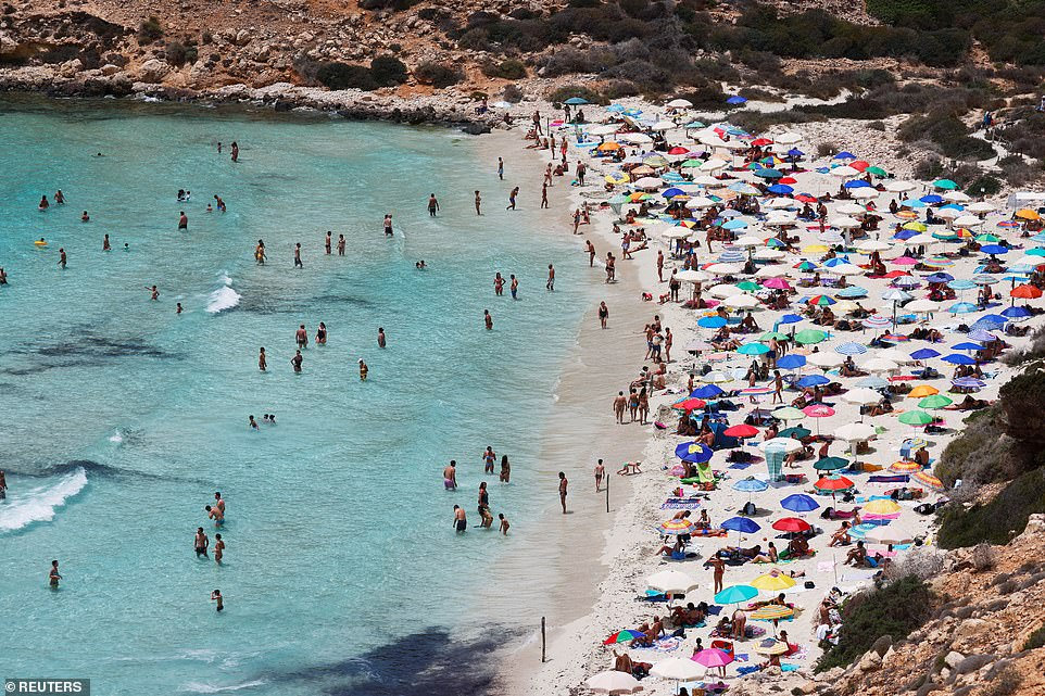 Fully vaccinated Britons could enjoy quarantine-free holidays from as early as July 19, the Mail can reveal today. Pictured:People sunbathe on the beach on the Sicilian island of Lampedusa, as a flow of migrants arriving on the Mediterranean island, in Lampedusa, Italy, June 22