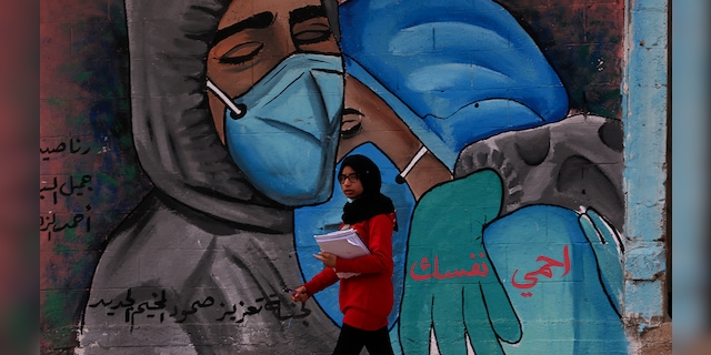 """A student walks past a mural encouraging the wearing of face masks amid the coronavirus pandemic, on the main road of Nusseirat refugee camp, central Gaza Strip, Tuesday, Nov. 24, 2020. Arabic message reads: """"Protect yourself."""" (AP Photo/Adel Hana)"""