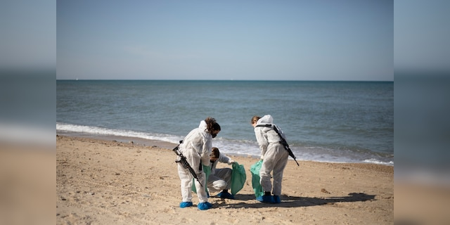 Israeli soldiers wearing protective suits clean tar from a beach after an oil spill in the Mediterranean Sea in Sharon Beach Nature Reserve, near Gaash, Israel, Monday, Feb. 22, 2021. (AP Photo/Ariel Schalit)
