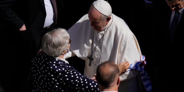 Pope Francis talks with Lidia Maksymowicz, a Holocaust survivor, who was a prisoner in the Auschwitz-Birkenau extermination camp before leaving San Damaso Courtyard at the Vatican for his weekly general audience, Wednesday, May 26, 2021. (AP Photo/Alessandra Tarantino)