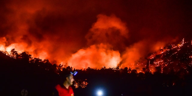 A man leaves as advancing fires rage the Hisaronu area, Turkey, Monday, Aug. 2, 2021. For the sixth straight day, Turkish firefighters battled Monday to control the blazes that are tearing through forests near Turkey's beach destinations.
