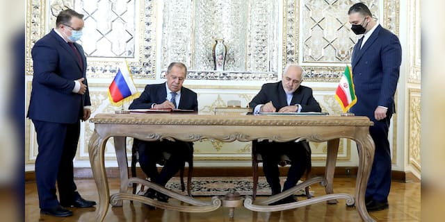 In this photo released by the Iranian Foreign Ministry, Iranian Foreign Minister Mohammad Javad Zarif, center right, and his Russian counterpart Sergey Lavrov, center left, sign agreements after their talks in Tehran, Iran, Tuesday, April 13, 2021. (Iranian Foreign Ministry via AP)